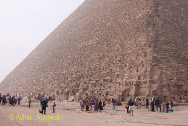 Cairo Pyramids - Side view of the Great Pyramid along with a number of tourist groups at the base