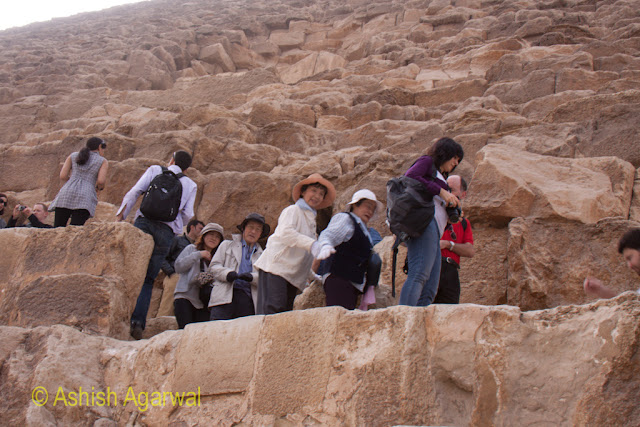 Cairo Pyramid - Tourists posing on a stone ledge of the Great Pyramid, waiting in a queue
