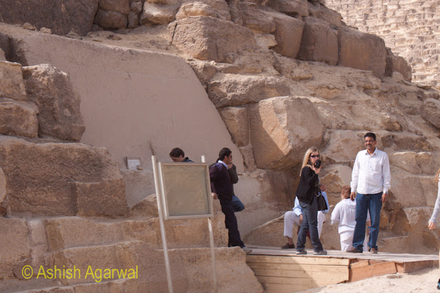 Cairo Pyramids - tourist standing on one of the platforms at the base of the Great Pyramid