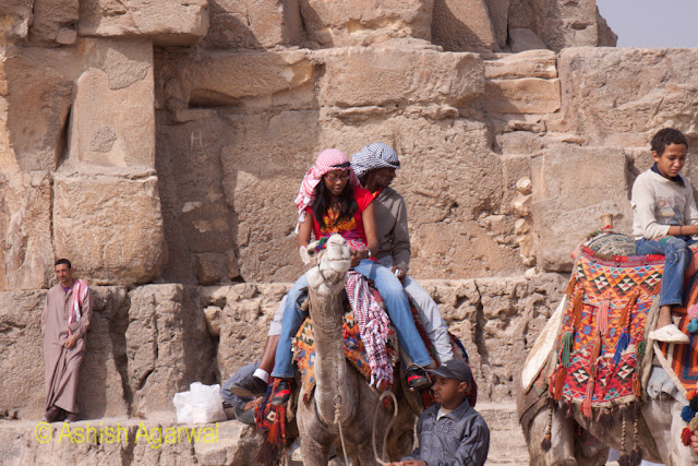 Cairo Pyamid - Tourist on top of a camel, with the Great Pyramid of Cheops right behind