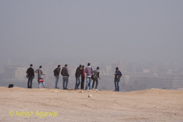 Cairo Pyramid - Young men standing on the edge of a small cliff, with a view of the suburb of Giza