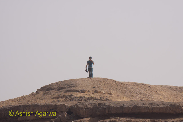 Tourist standing on top of a hillock in the desert, near the Great Pyramids