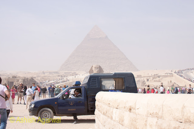A police vehicle in front of The Sphinx and the Great Pyarmid in Giza