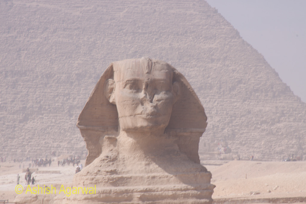 View of the full face of the Sphinx, with the structure of the Great Pyramid in the background