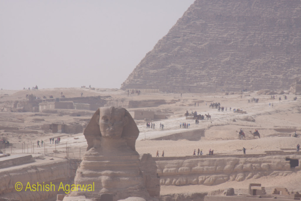 The Great Sphinx and the side of the Pyramid, along with a number of tourists on the ground