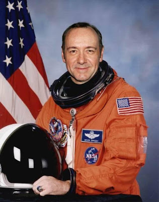 Kevin Spacey in a space suite and an orange pant suit