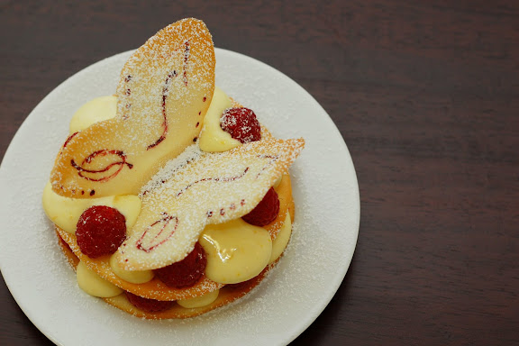 Butterfly vanilla tuile topping meyer lemon mousse with raspberries