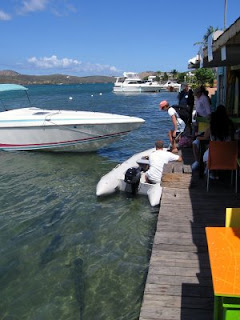 Nan getting into the dinghy with John at the Dinghy Dock while the giant tarpon look on