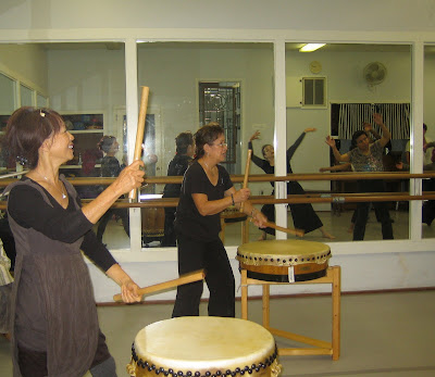 Members of Hawa, Drumming. L. Vera Leo, Center, Annie Ong Class dancing as seen through wall mirrors.