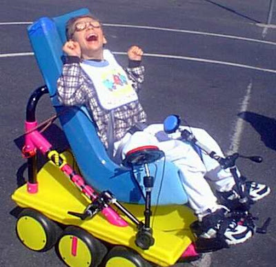 Cooper Car. Image of a small brightly coloured six-wheeler mini-space buggy. Controlled by two able-net switches with a young lad grinning broadly whilst controlling the car.