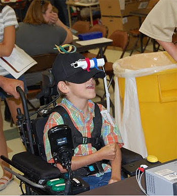 Image of a young boy playing a Wii game, using a cap with velcro straps to keep the Wii remote in place for head play.