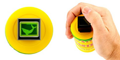 D.I.Y. One Switch Hand Held Game. Image of a yellow sweet pot - adapted with an all in one screen and push button - with a picture of a green fish displayed.