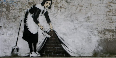Stencilled Banksy image of a cleaner pulling up the wall as if it was a curtain, and dusting away.