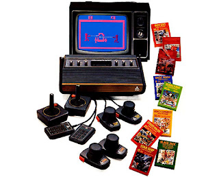 1977 Image of an Atari VCS games console playing Outlaw on a 70's Colour TV surrounded by controllers and game boxes.
