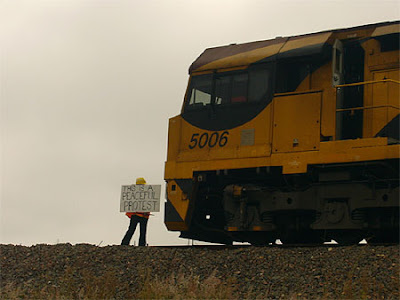Image of a lone protester stopping a train in its tracks, holding a plackard that reads 'THIS IS A PEACEFUL PROTEST'.