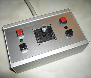 Image of an analogue joystick, boxed and surrounded by four mounted digital buttons.