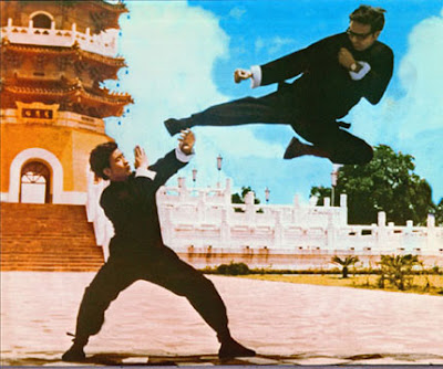 Image of two martial artists, one blocking the other executing a flying kick in front of an ancient Pagoda.