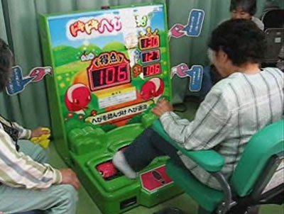 Image of an elderly person playing a form of whack-a-mole but with their feet.