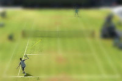 Mock-up image of a grass tennis court, where all is blurred but for the two tennis players, the ball, and a small part of the net.