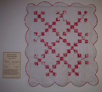 red nine patch quilt with scalloped edges