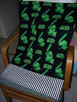 dark green pillowcase with the words Star Wars and the image of Yoda finished with black and white stripes