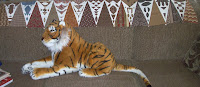 row of triangles on back of couch with big, stuffed tiger under it