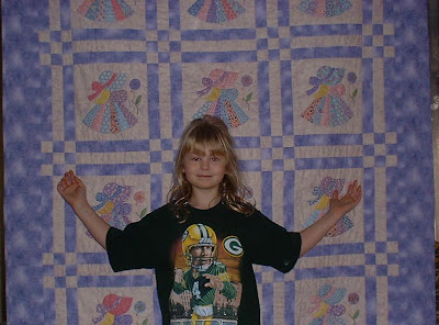 Abby in front of the quilt I made her for Christmas