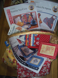basket filled with patterns and fabrics for the apron and tea cozy