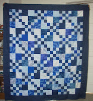 Four Patch quilt top done with different shades of blue fabrics
