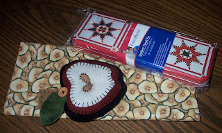 apple pincushion, apple fabric and tin pencil holder with quilting design on it
