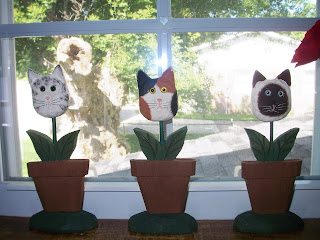 three wooden flower pots each growing a cat's head