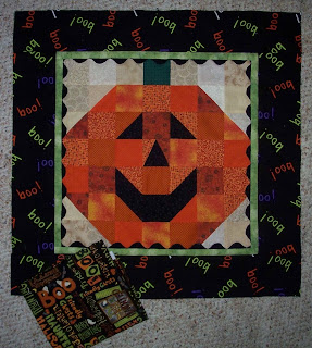 pumpkin with smiling face, narrow lime green border with black rick rack and a 3 inch black border with BOO written in different colors