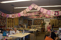 Inside of the shop showing several clothesline rows with pink banners hanging from them
