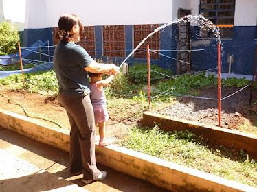 Profª Fátima e aluninha regando os canteiros