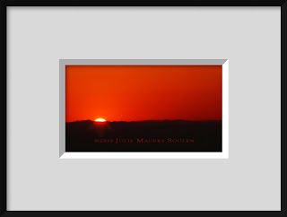 A framed photo of a brilliant red sunrise is an abstract explosion of bright red with a silhouette of the horizon.