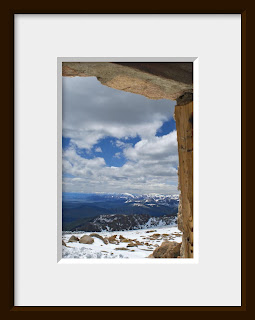 A framed photo of looking out a rustic window from the ruins of a chalet at the very top of Mount Evans at an elevation of 14,264' shows a scenic mountain landscape as far as the eye can see.