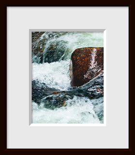 A framed photo of swirling and turbulent frigid mountain water careens by a large boulder