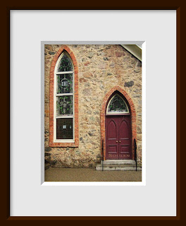 The burgundy doors and stained glass window of a stone Gothic church are outlined with beautiful brick arches.