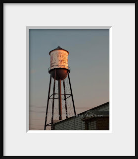 Old water tower with sunset glow in frame.