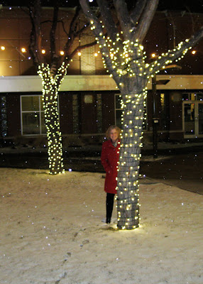 Julie in red coat behind tree with mini lights.