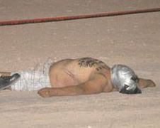 Another Body, Taped Head, and Warning on Chest.  Photo El Mexicano