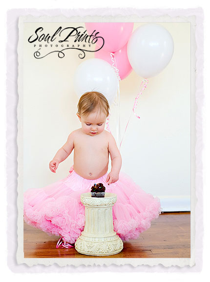 Cute baby girl birthday photos while cutting cake