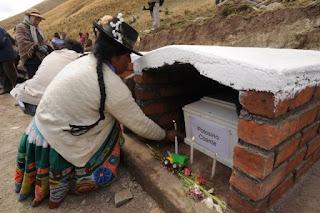 Una mujer enciende una vela en la tumba de su sobrino durante el entierro de víctimas de la masacre de Putis en 1984
