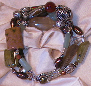 grossular garnet, ocean jasper, pearl, serpentine, carnelian, goldstone, quartz, aquamarine and sterling silver