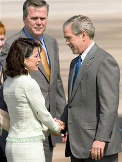 Bush with Katherine Harris, the Florida Secretary of State who employed various means of vote fraud to guarantee his 2000 presidential appointment