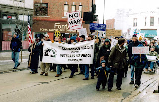 "Members of the Madison chapter of Veterans for Peace, February 1, 2003. The guy with the blue hat was a bombardier in the firebombing of Tokyo in World War II. The guy with the ""No war"" sign was a combat journalist in ""Vietnam."" The guy with the beard, holding the corner of the banner was an artilleryman in ""Vietnam."" Photo credit: John Hamilton"