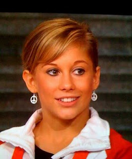 Shawn Johnson wearing peace symbol earrings after winning gold