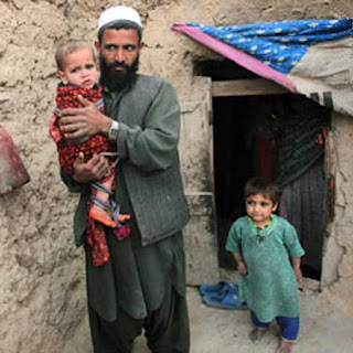 "A wary ""Afghani"" father contfronted by ""American"" soldiers at his home"