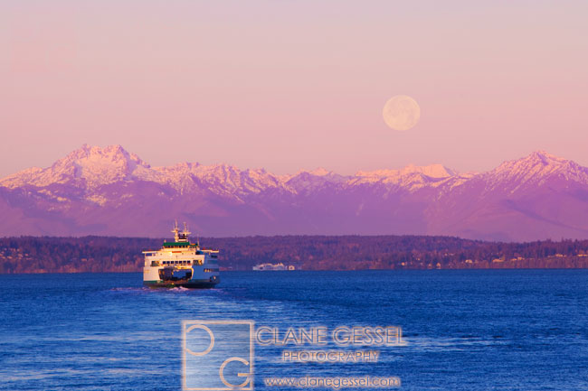 Ferry heading towards the olympic mountains with a full moon