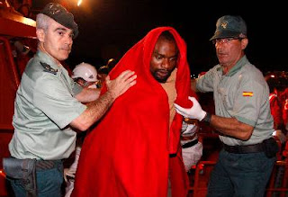 Miembros de la Guardia Civil ayudan a uno de los inmigrantes que llegaron al puerto de Almería tras ser rescatados de la patera en la que viajaban por Salvamento Marítimo. EFE
